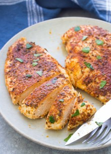 Sliced baked chicken breast with seasoning on a plate.