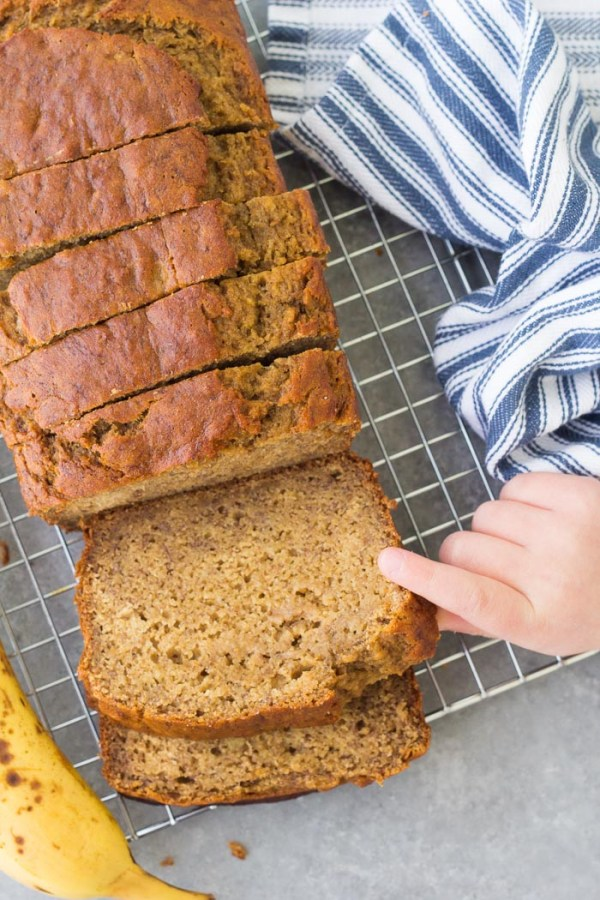 The best healthy banana bread recipe. A loaf of sliced banana bread with someone grabbing a slice.