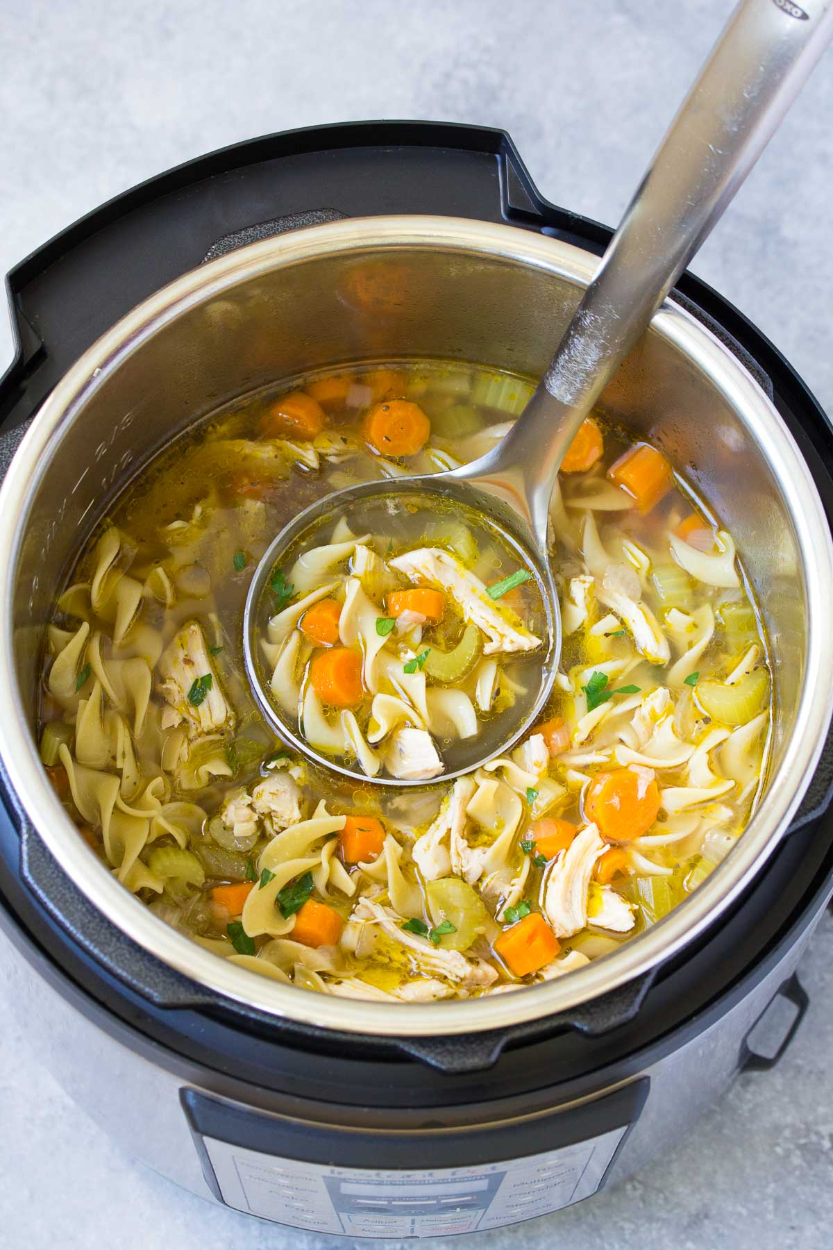 instant pot chicken noodle soup in an instant pot with a ladle