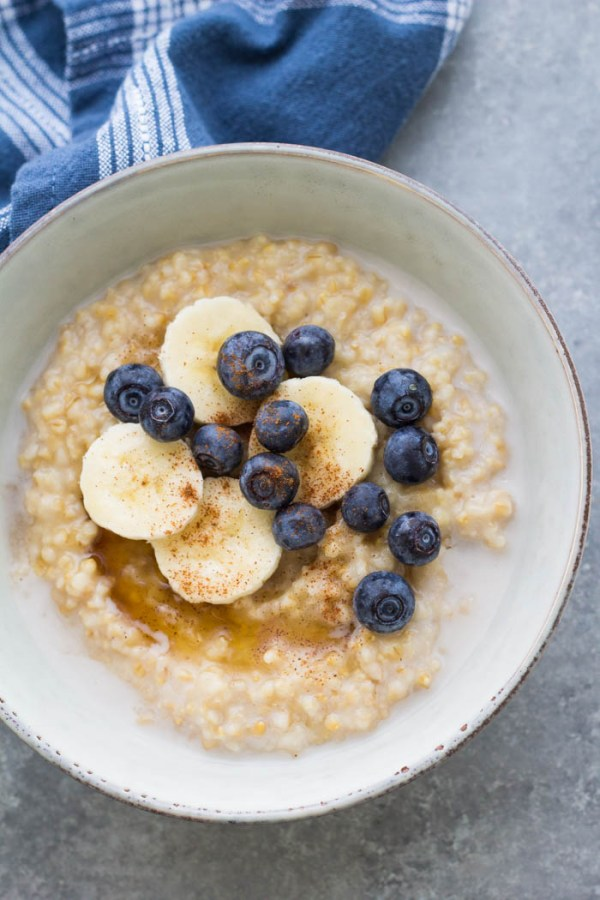 Instant Pot steel cut oatmeal in a bowl with maple syrup, banana and blueberries.