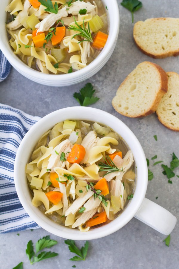 Two bowls of crockpot chicken noodle soup served with french bread.