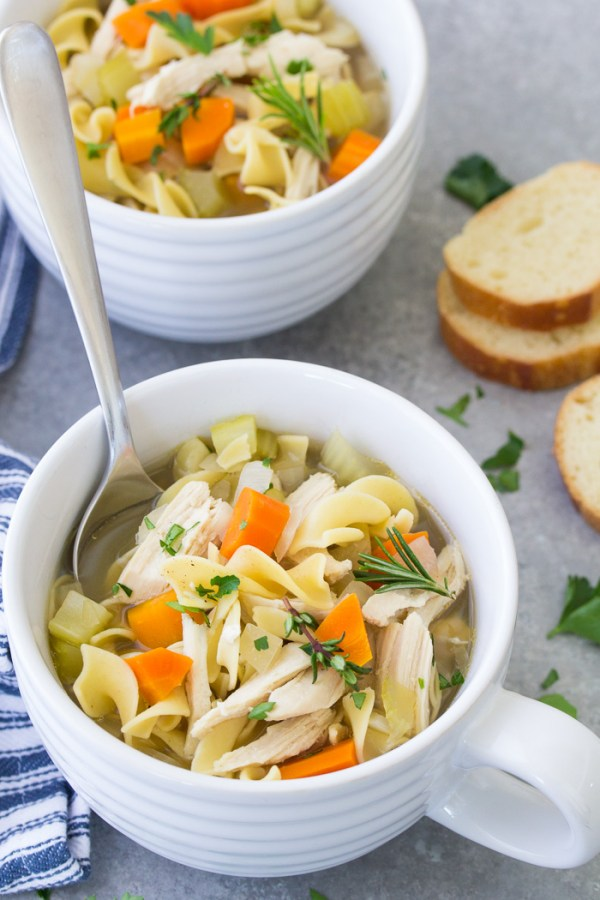 Homemade crock pot chicken noodle soup in a bowl with a spoon. Easy from scratch slow cooker soup recipe.