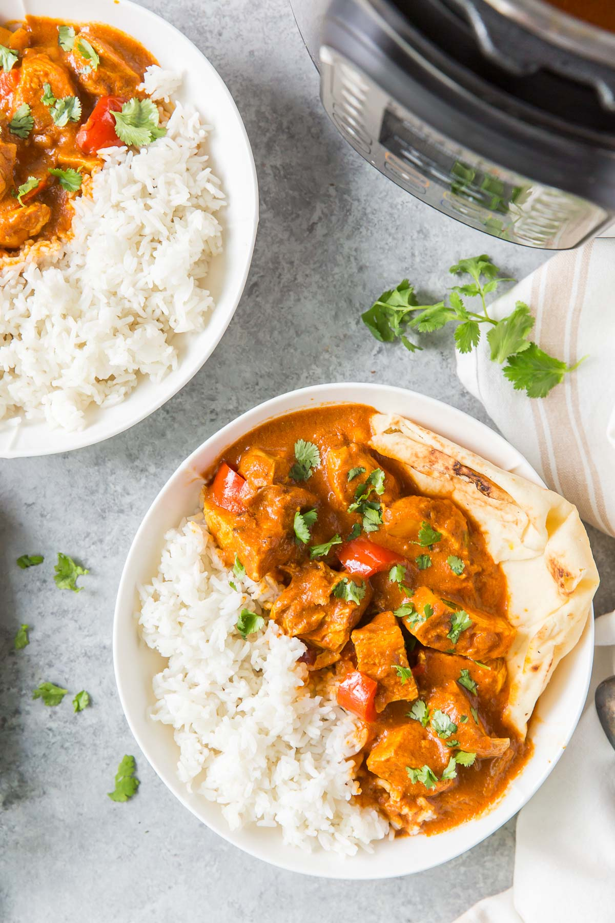 butter chicken with rice in serving bowls by an instant pot