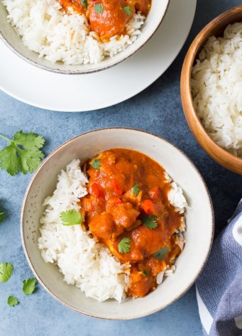 Two bowls of Instant Pot butter chicken served with rice.