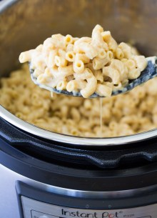 Creamy Instant Pot mac and cheese on a serving spoon over an Instant Pot.