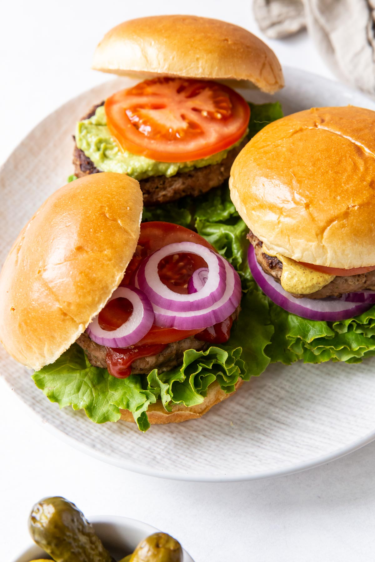 three turkey burgers served on buns with a variety of toppings