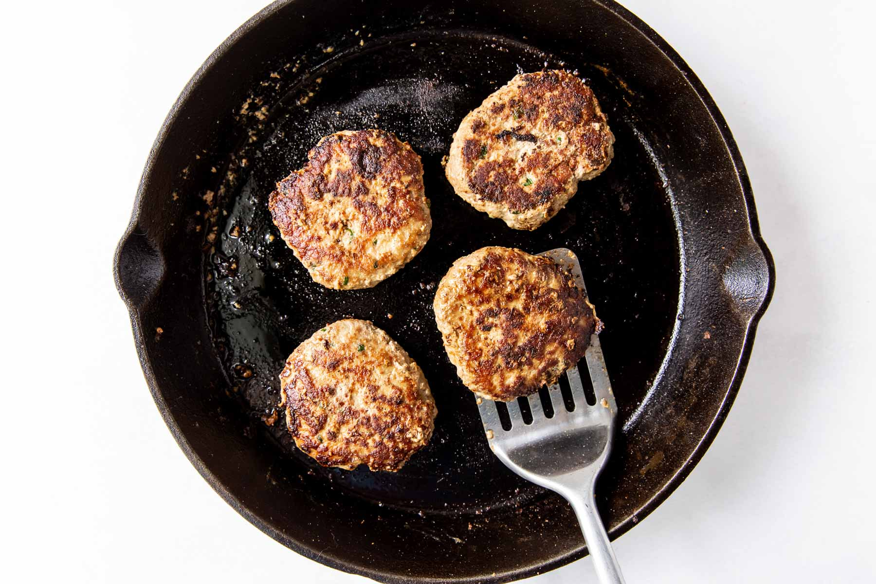 turkey burgers in a cast iron skillet with one burger on a spatula