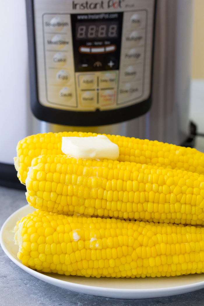 pressure cooked Corn on the cob with butter in front of an Instant Pot.