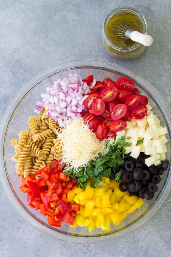 Ingredients for Italian pasta salad in a bowl, with a jar of dressing behind the bowl.
