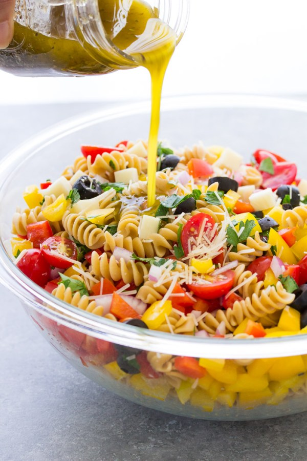 Pouring dressing over Italian pasta salad.