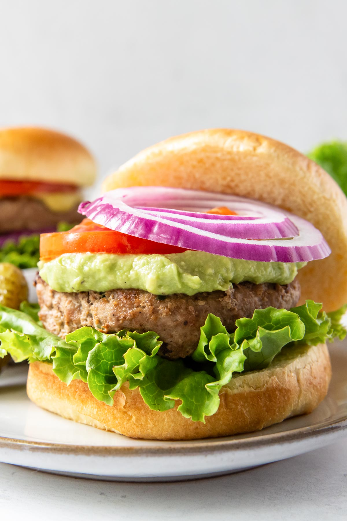 turkey burger served on a bun with lettuce, guacamole, tomato and red onion