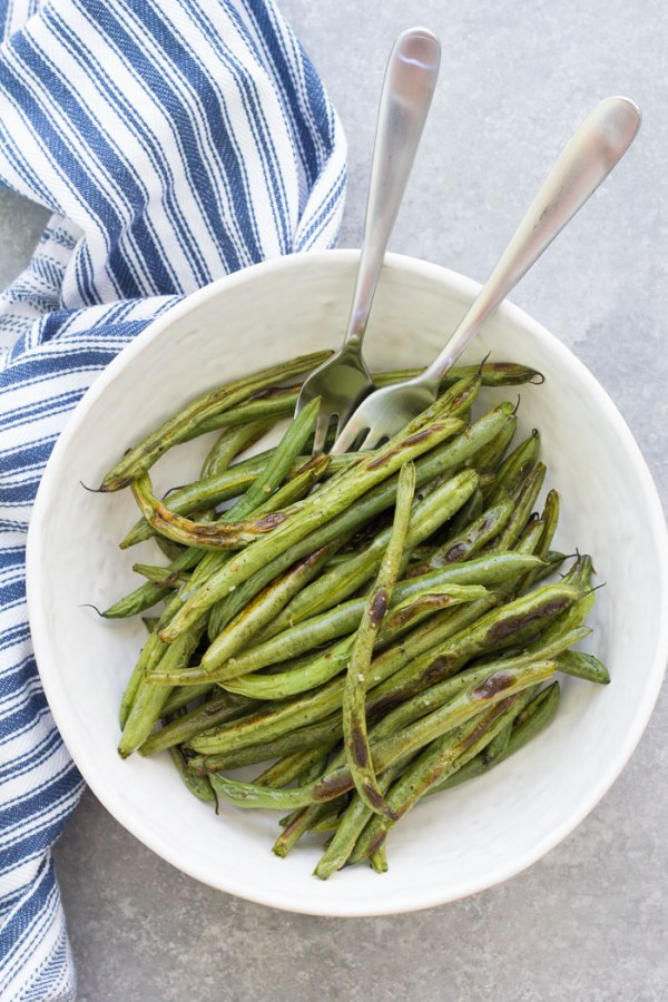 Oven roasted green beans in a serving bowl with two forks.