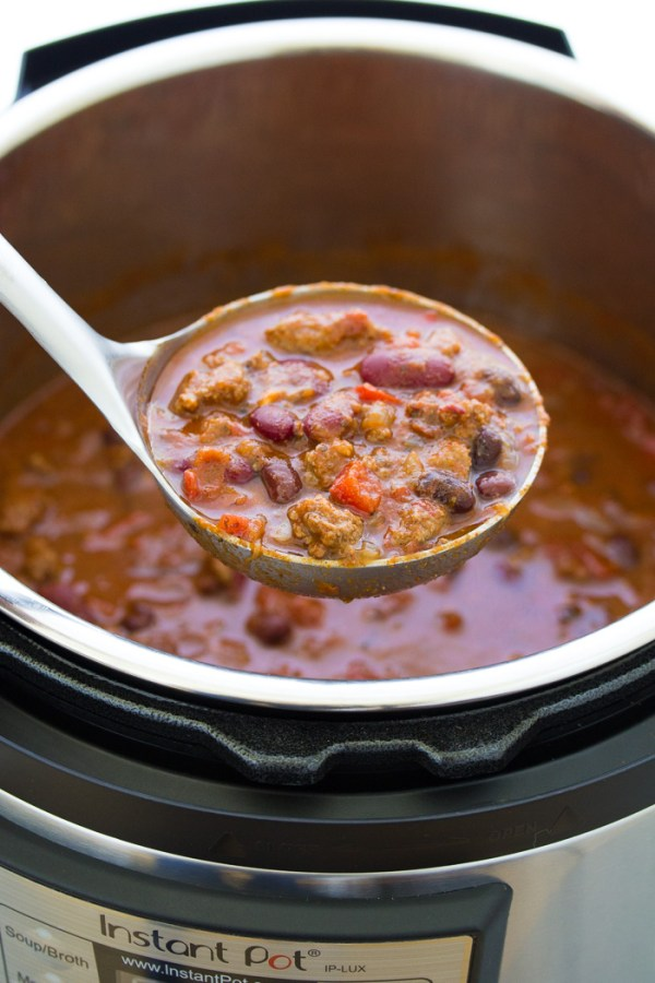 Beef chili in a ladle over an Instant Pot pressure cooker.