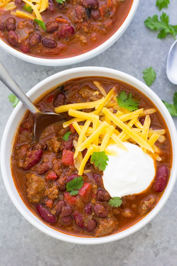 Two bowls of Instant Pot chili, with toppings and a spoon.
