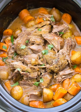 Slow Cooker Pot Roast in a crock pot, with tender fall apart beef, carrots, potatoes and gravy.