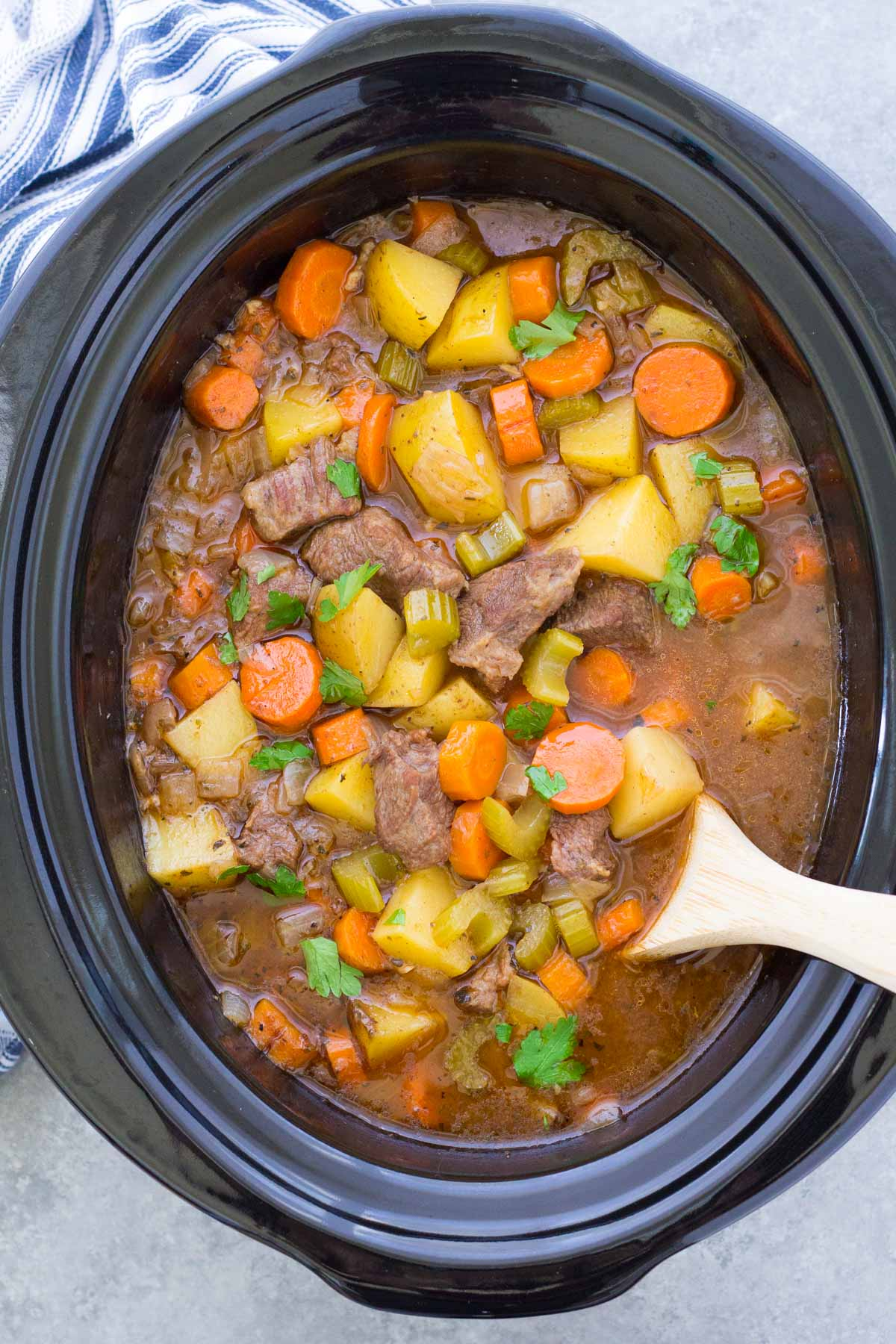beef stew in a slow cooker with a wooden spoon