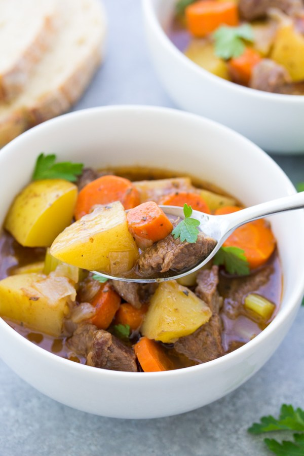 A spoonful of beef stew made in the crockpot, with bowls of stew in the background.
