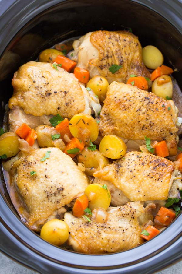 Close up of chicken thighs in a slow cooker, with carrots and baby potatoes.