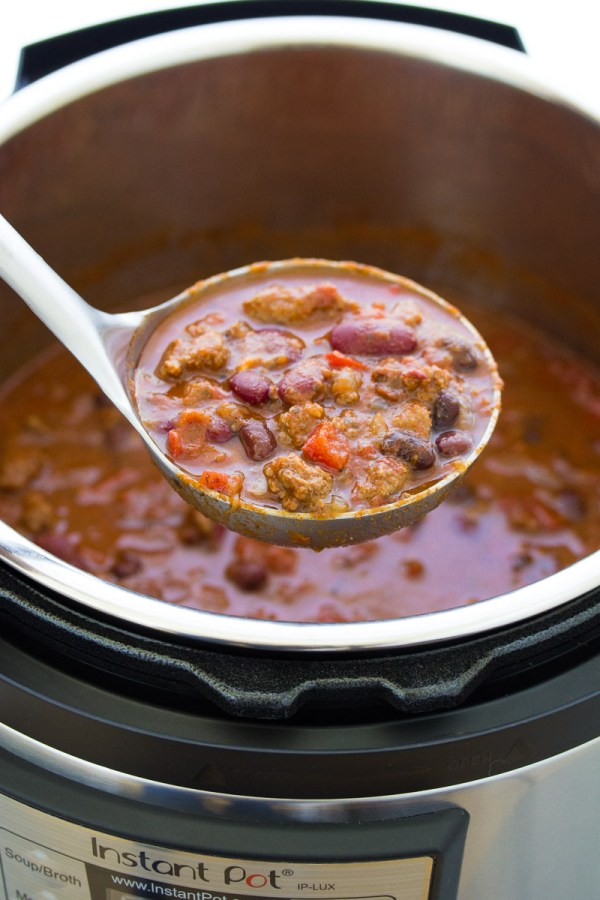 A ladle with chili held over an instant pot.
