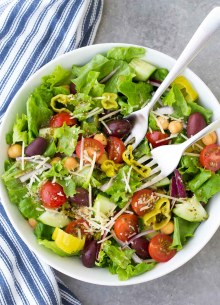 Italian salad with tomatoes, cucumber, olives and parmesan cheese in a white bowl with two forks.