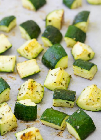 Cubes of roasted zucchini with seasonings on a baking sheet.