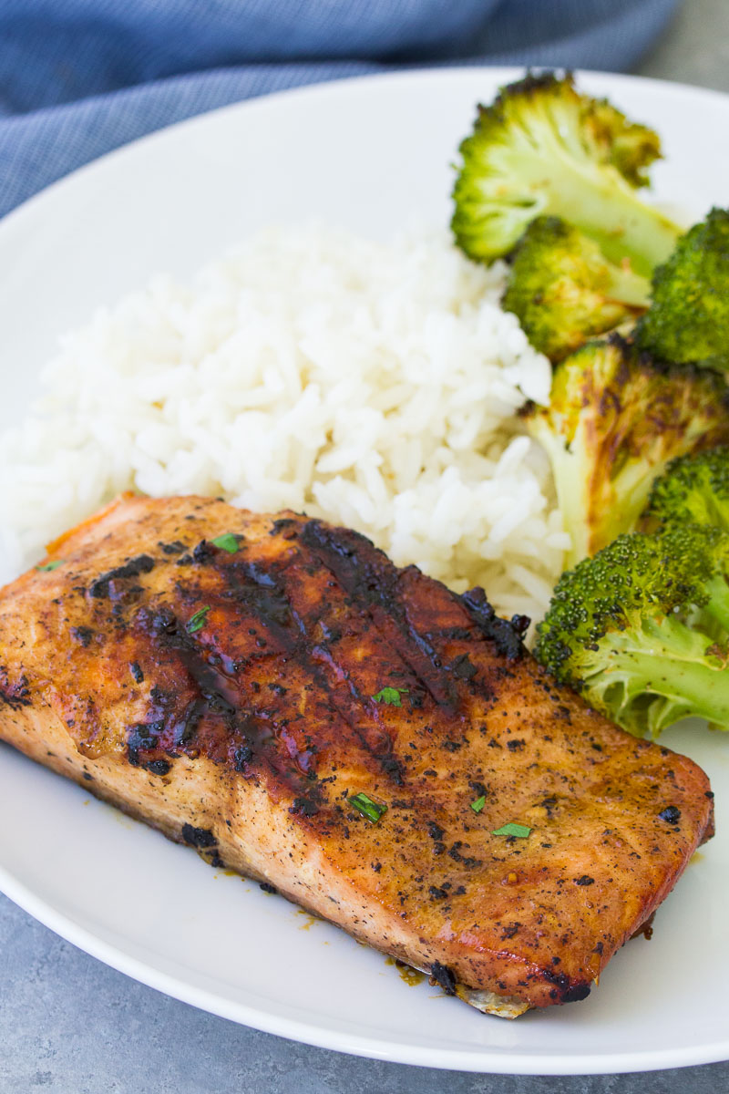 Grilled salmon on a white plate with rice and broccoli.