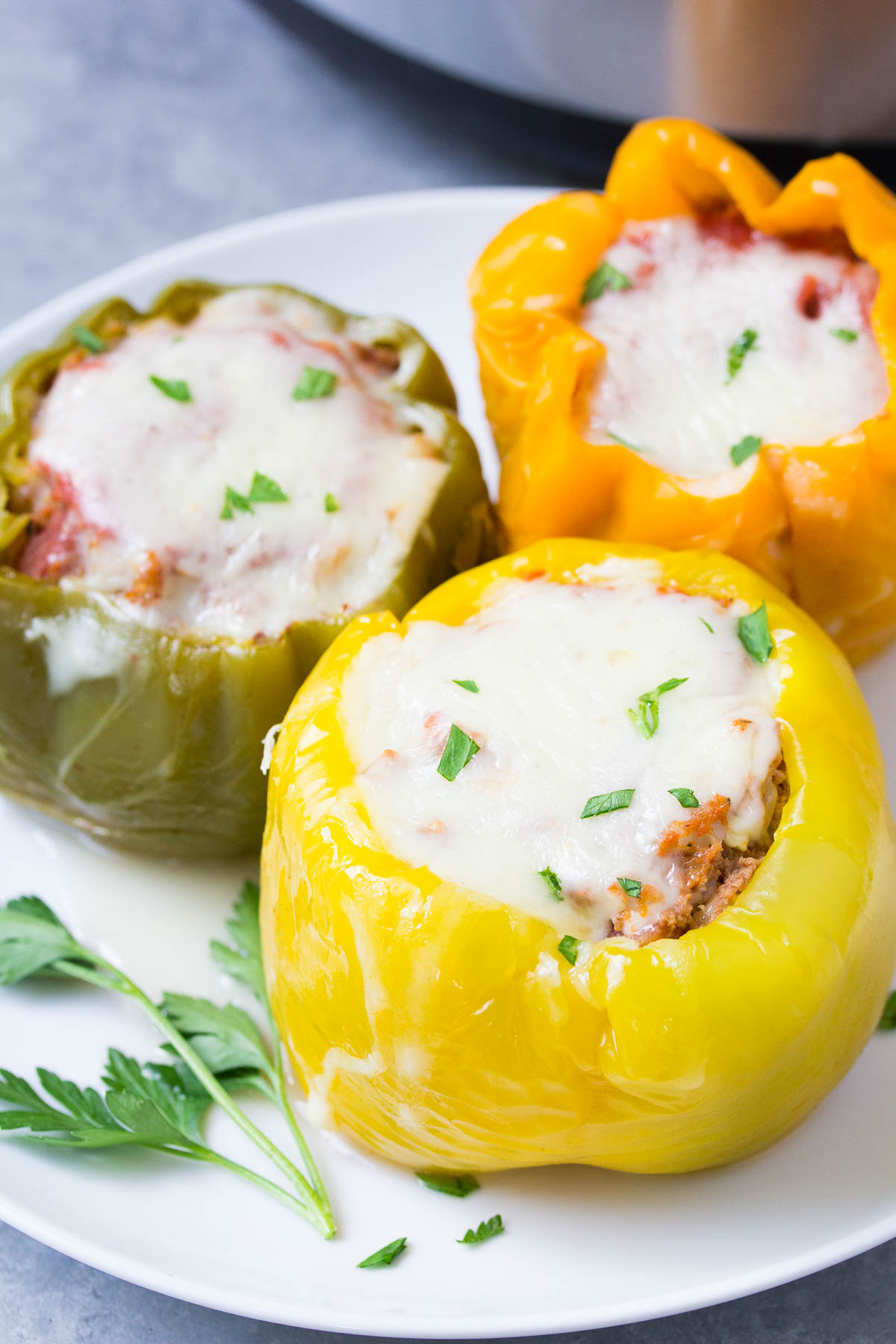 Three stuffed peppers with cheese on a white plate.