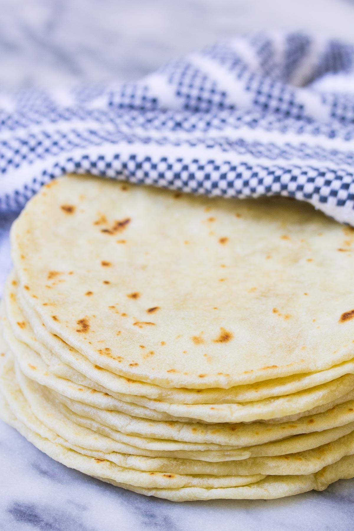 Homemade flour tortillas stacked together.