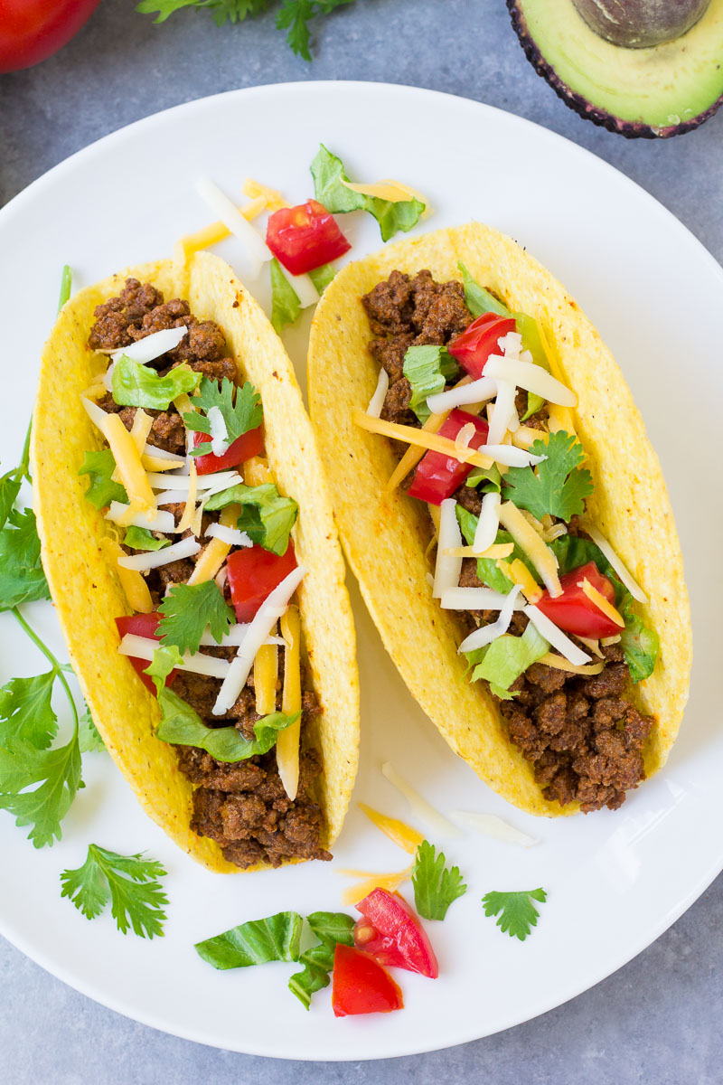 two crispy ground beef tacos with lettuce, tomato and cheese