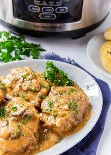pork chops smothered with gravy on a plate with slow cooker in background
