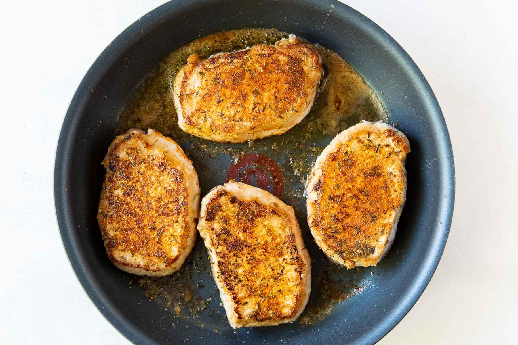 browning pork chops in a skillet