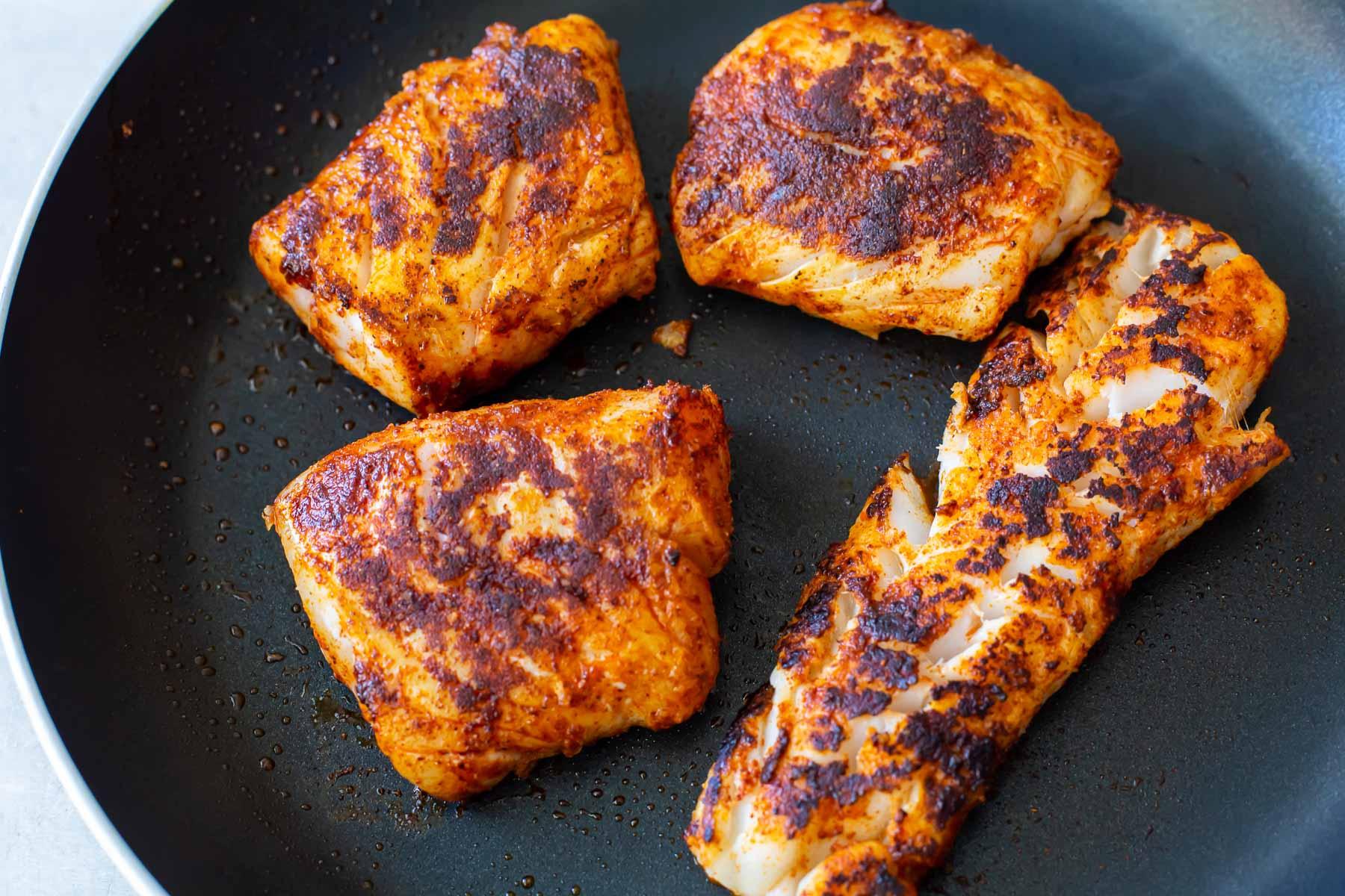 cooking seasoned cod in a skillet
