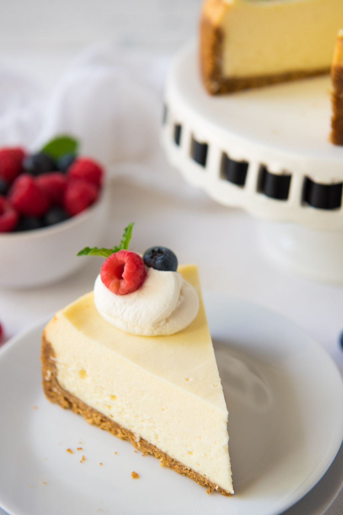 slice of instant pot cheesecake topped with whipped cream and berries