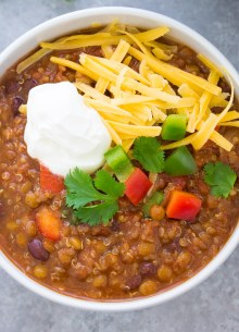 lentil chili with toppings in a white bowl