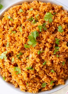 mexican rice in serving bowl garnished with cilantro and lime