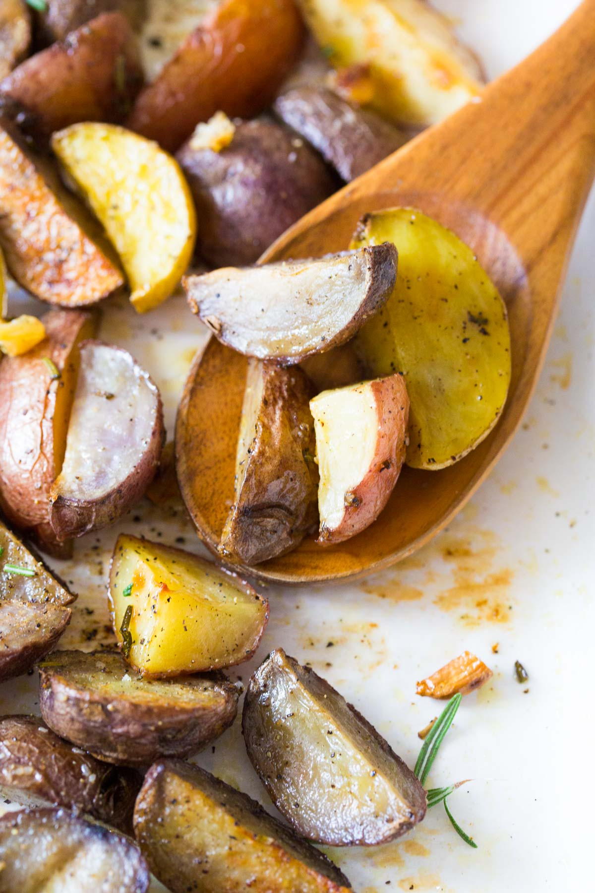 roasted potatoes with a wooden spoon on baking sheet