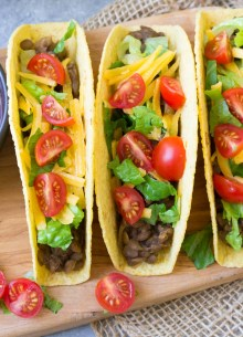three lentil tacos with lettuce, tomato and cheese