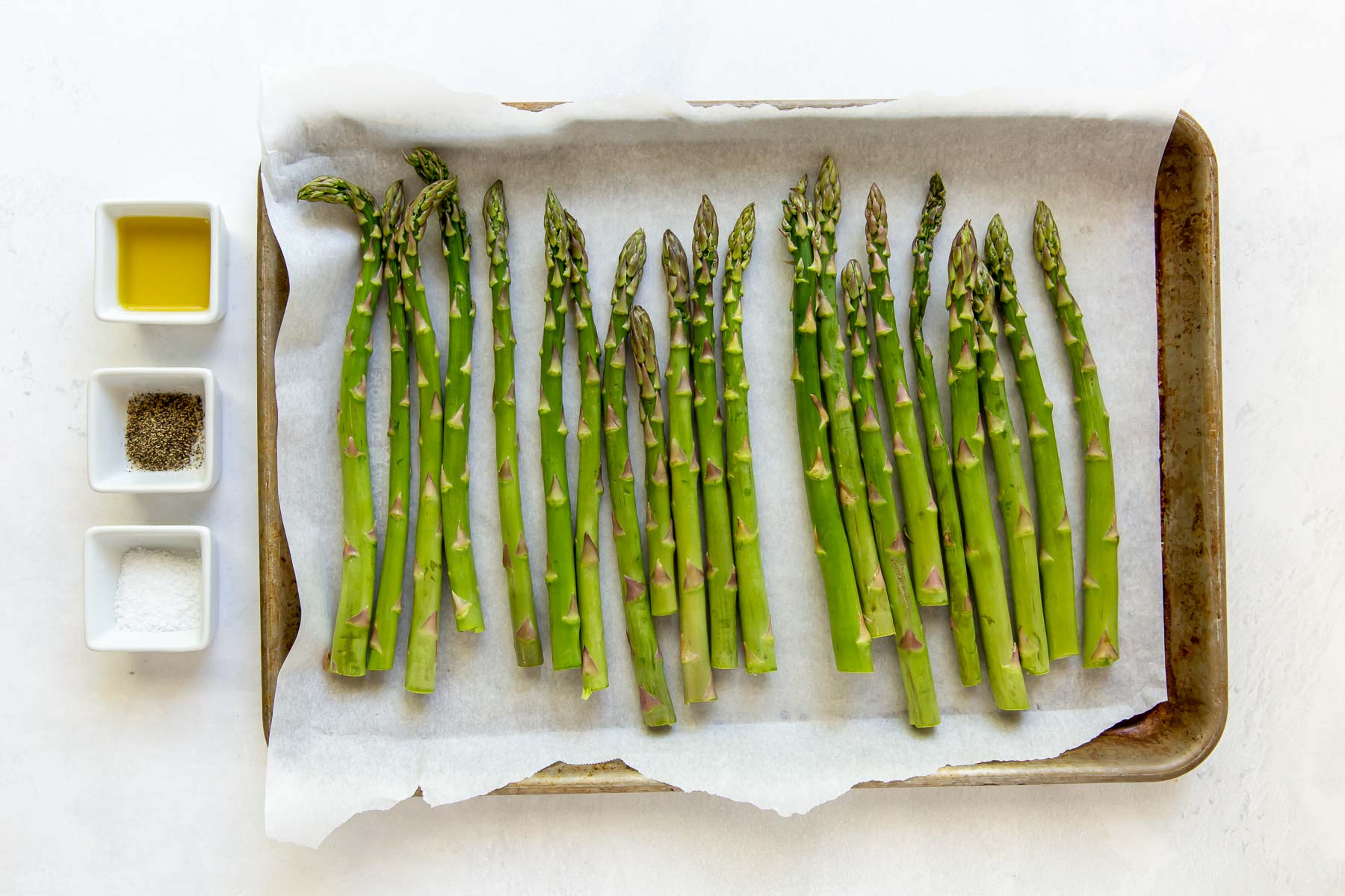 fresh asparagus on baking sheet with dishes of olive oil, salt and pepper on the side