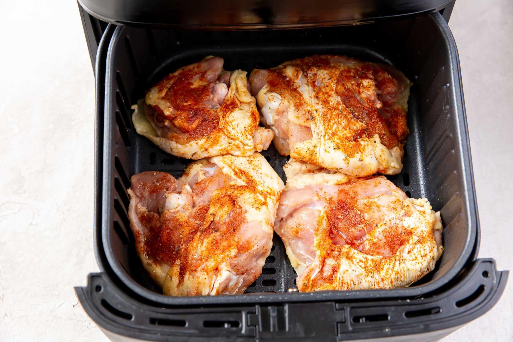 uncooked chicken thighs skin side down in air fryer