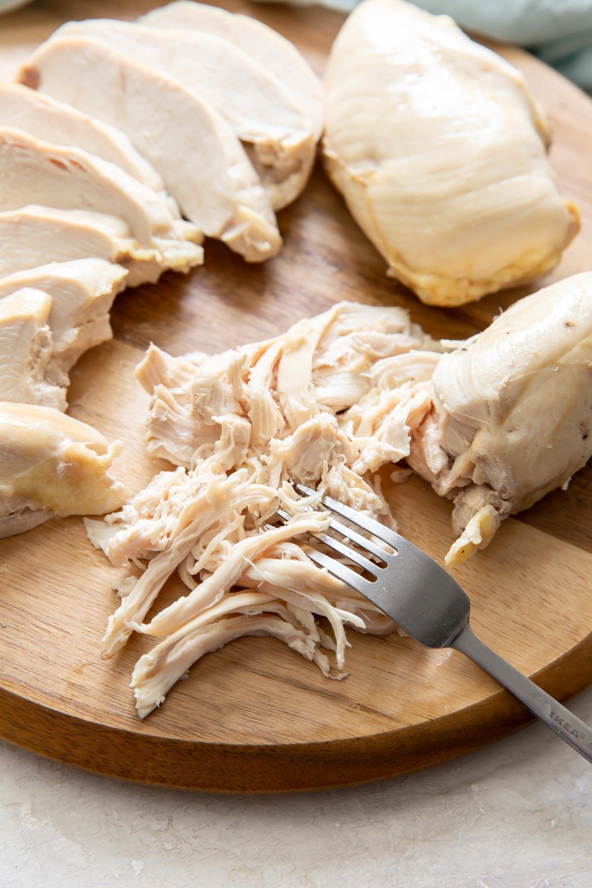 partially shredded chicken breast with sliced chicken in background