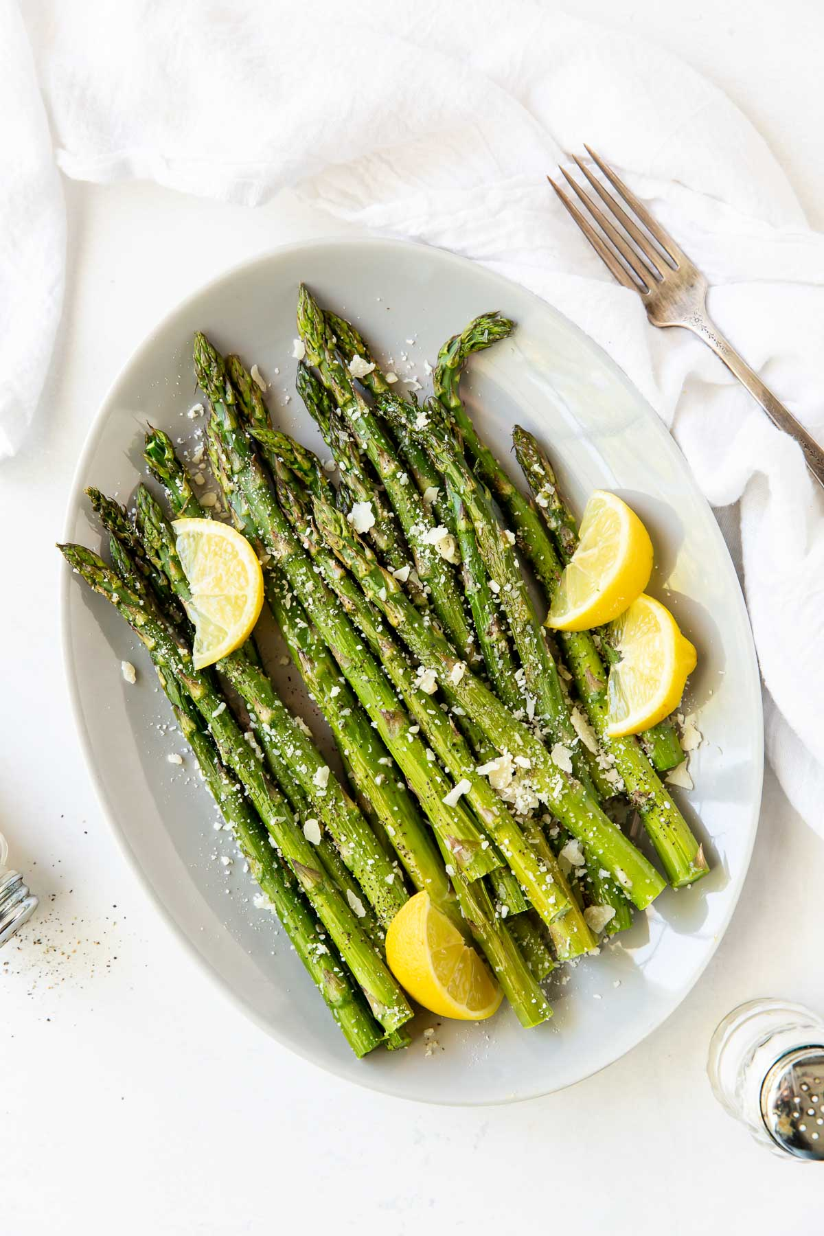 roasted asparagus with lemon and parmesan on a white oval serving plate