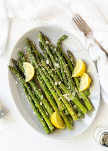 roasted asparagus with lemon and parmesan on a white oval plate