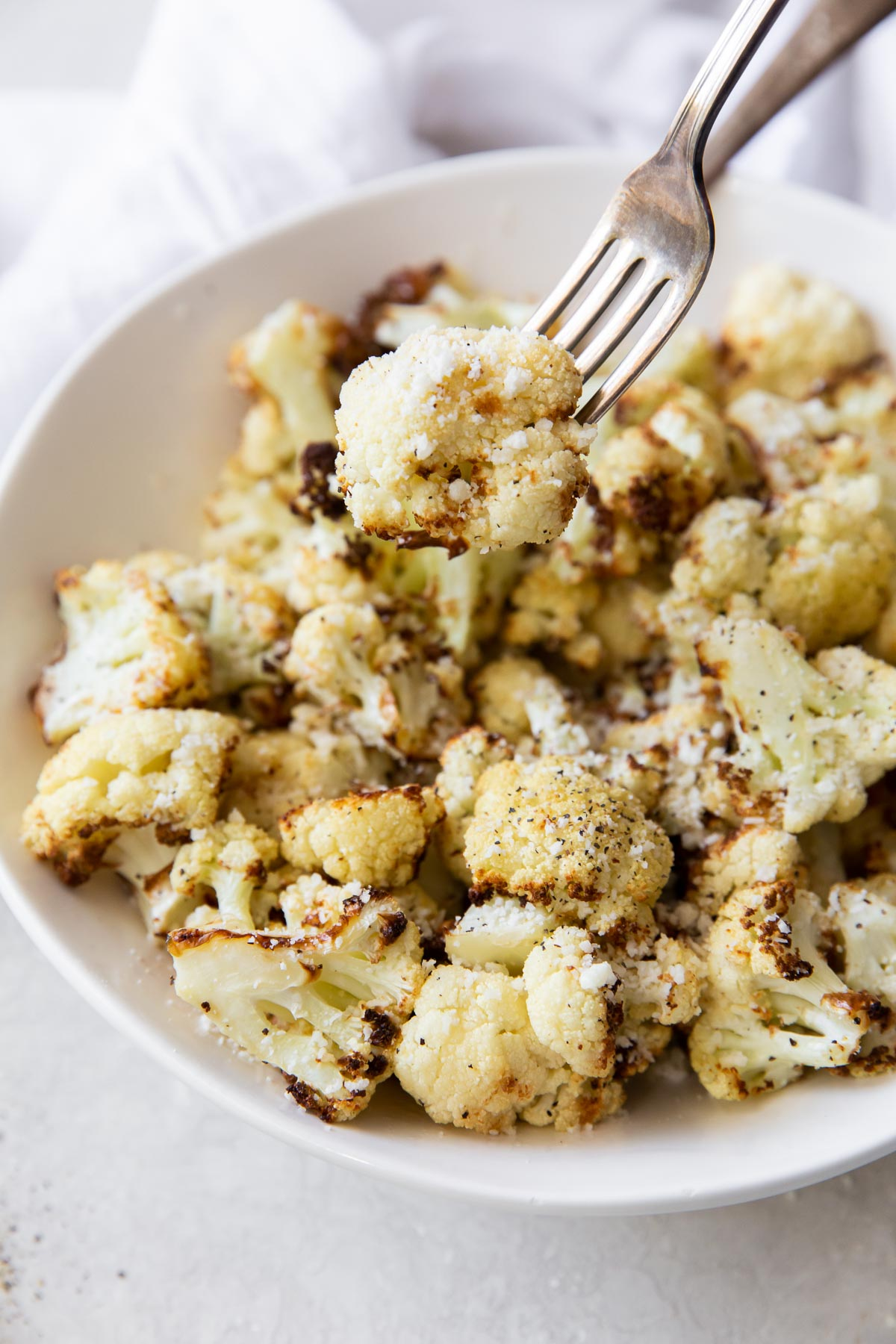 bite of cauliflower on a fork held over a bowl of cauliflower