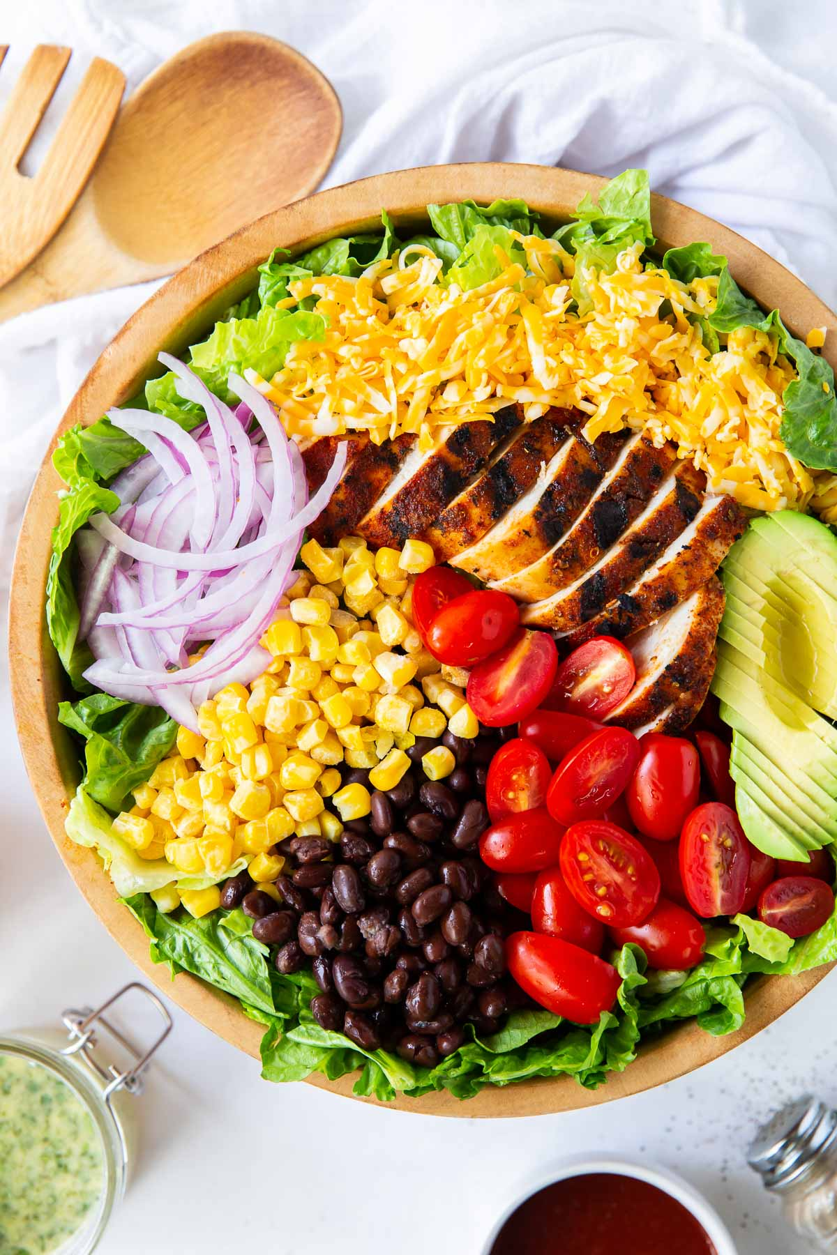 lettuce, grilled chicken and other salad ingredients in large bowl