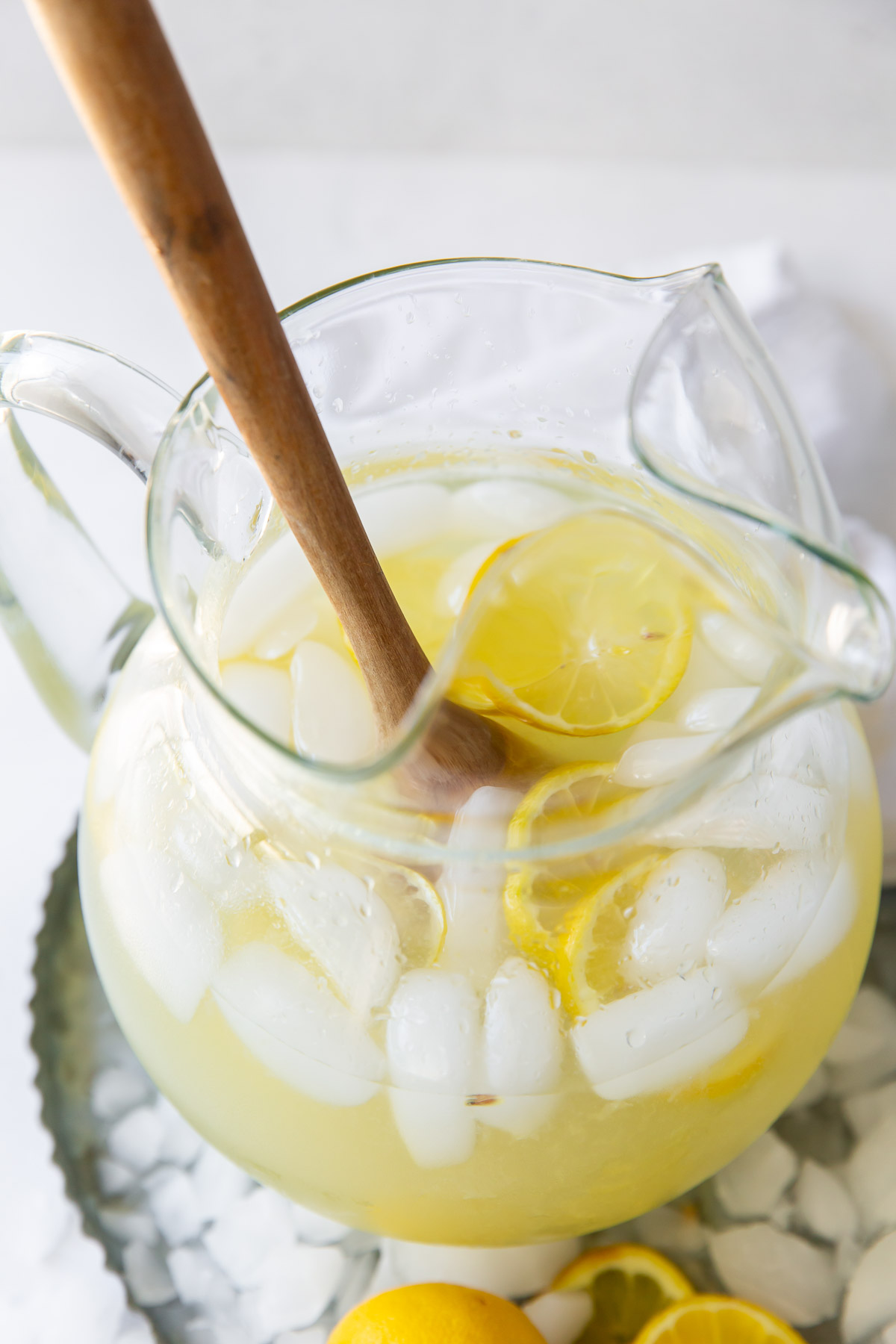 homemade lemonade in a pitcher with ice, lemon slices and a wooden spoon