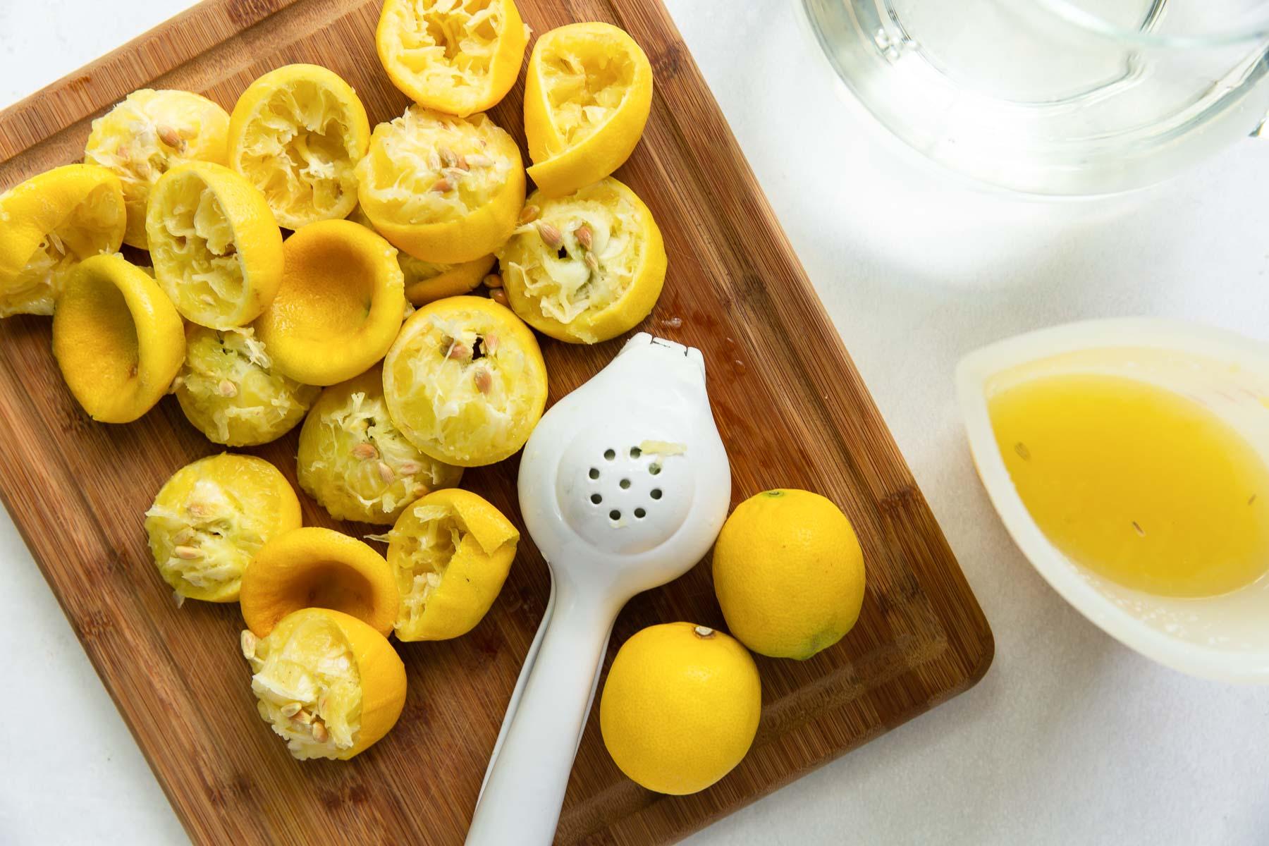 juiced lemons and juicer on a cutting board for lemonade