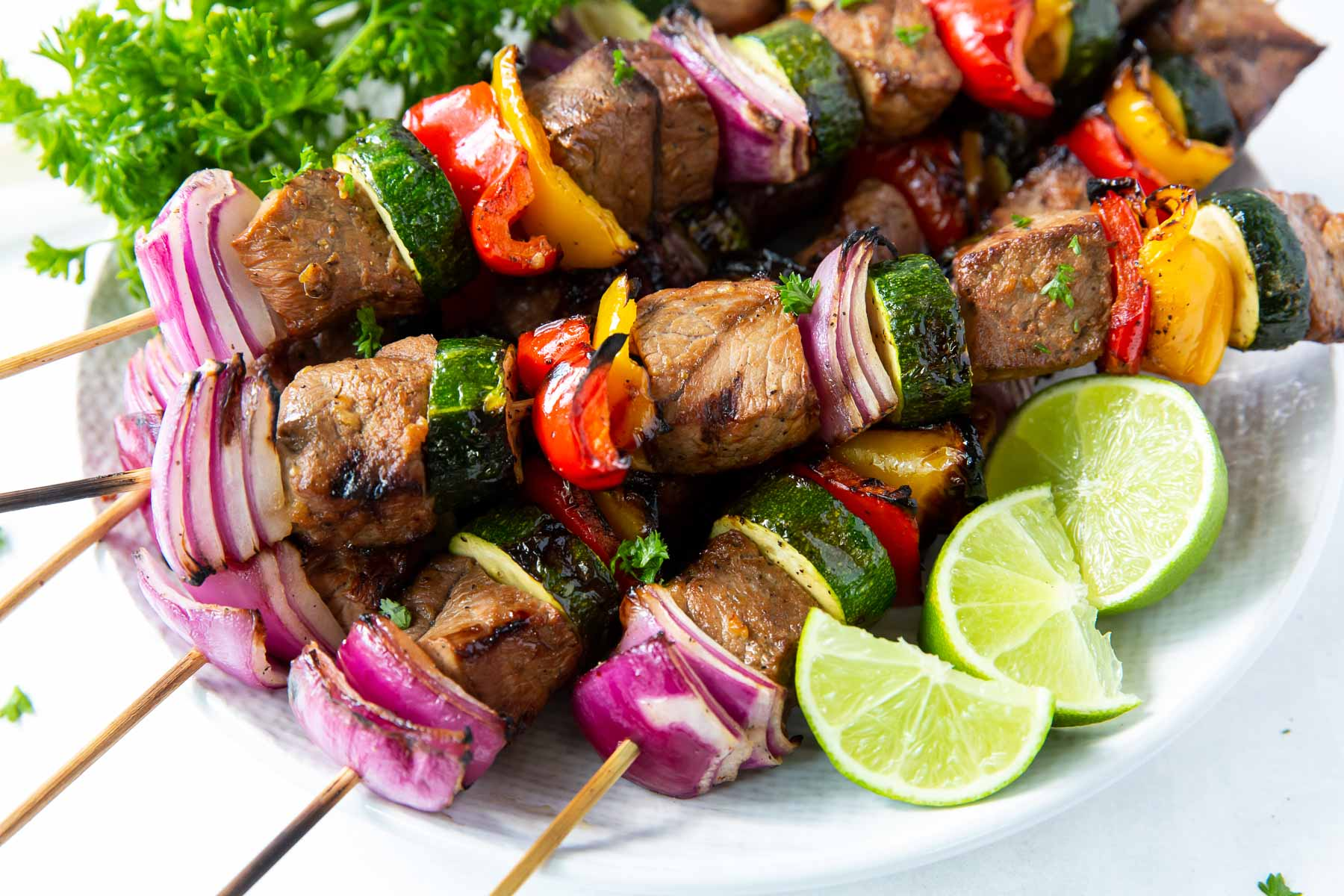 kabobs stacked on a plate with lime wedges