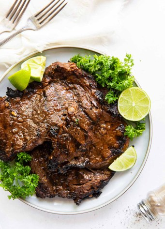 two grilled ribeye steaks on a plate with parsley and lime garnish