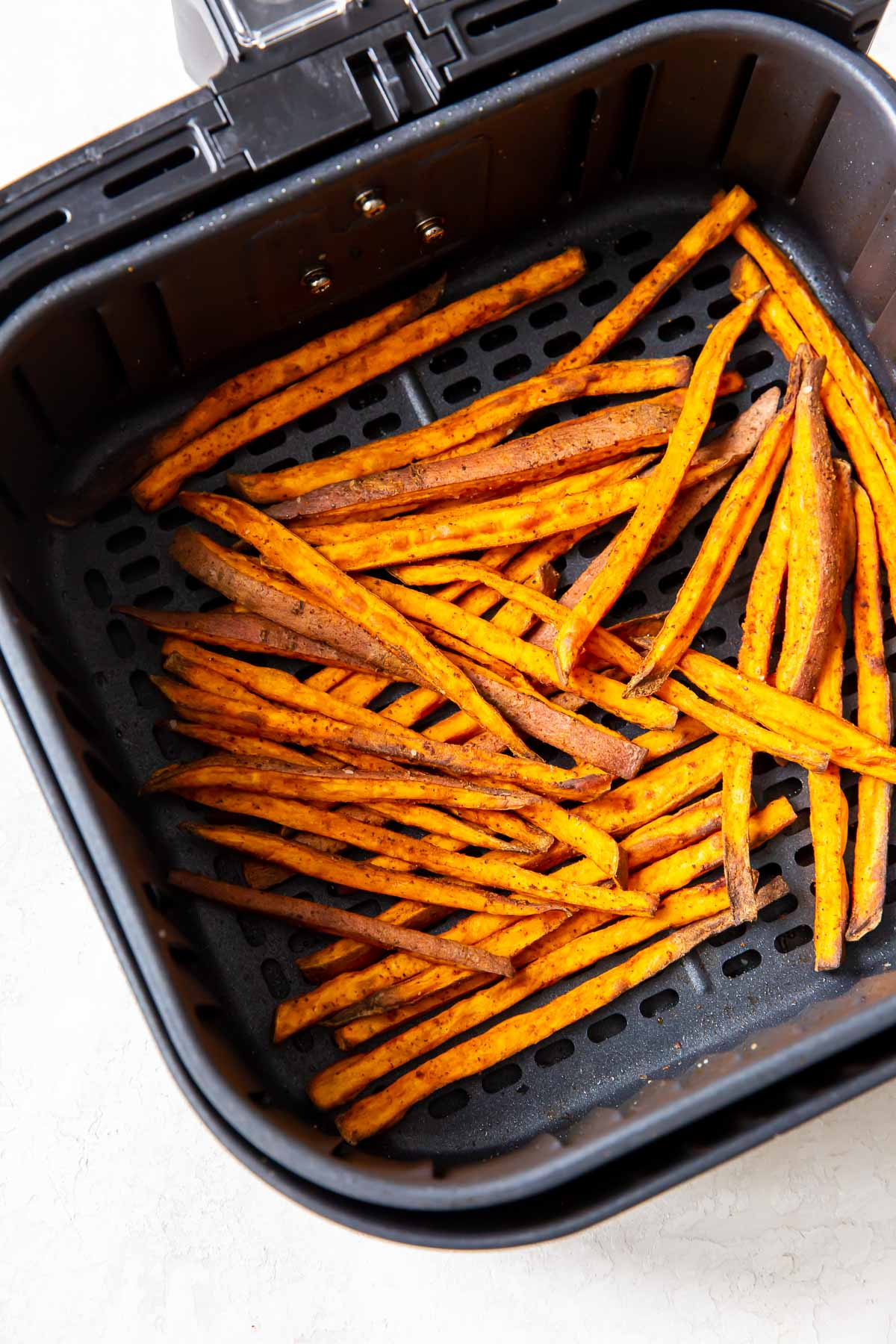 cooked sweet potato fries in air fryer basket