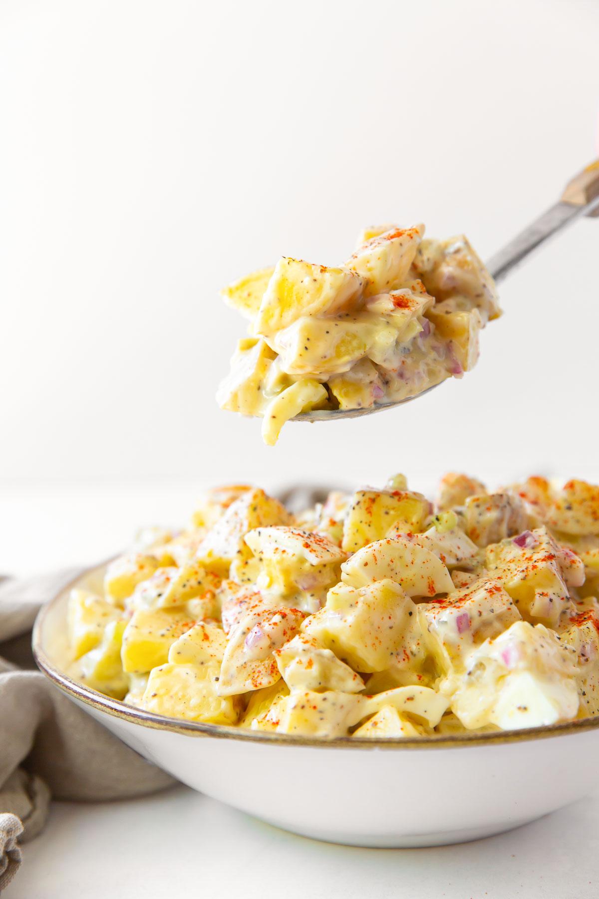 potato salad on a serving spoon held over a bowl of potato salad